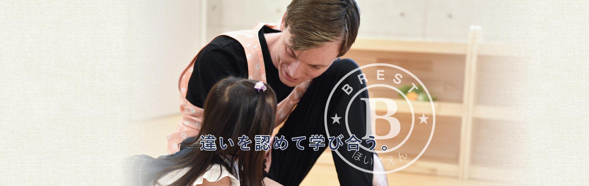 英語を話しながら、子どもと一緒に遊んでいる外国人講師のバナー